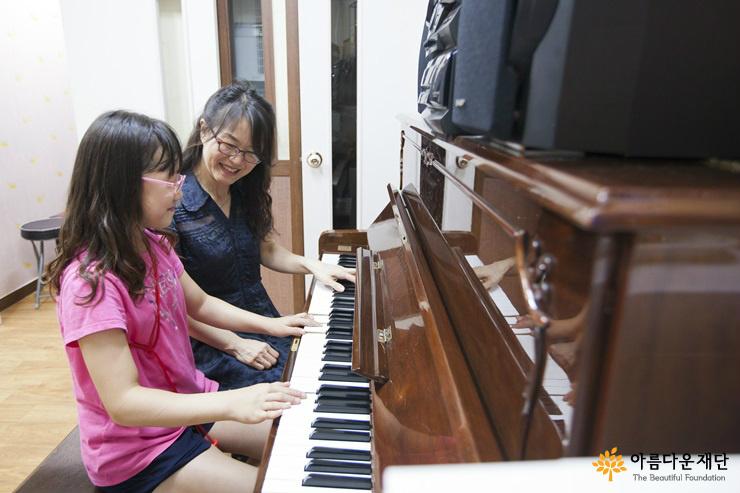 김서연 원장과 아이가 즐거운 표정으로 피아노를 연주하고 있다.