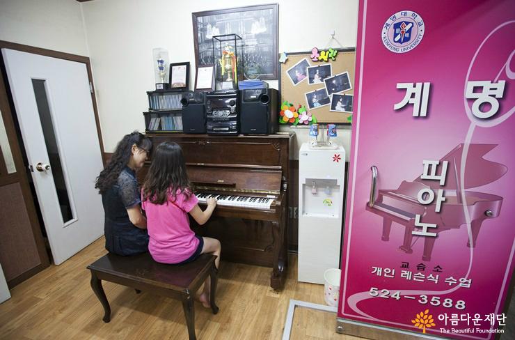 아이와 함께 피아노를 연주하는 개인레슨 풍경