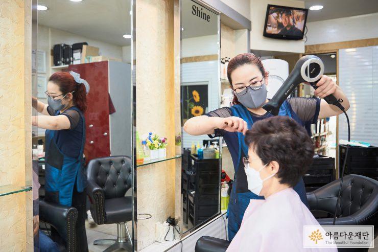 문현정 창업주가 손님의 머리를 드라이하고 있다